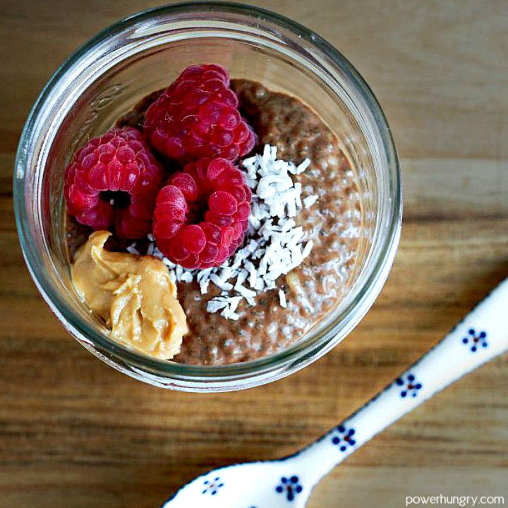 chocolate chia pudding with nut butter, raspberries and shredded coconut on top