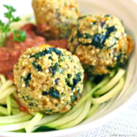 high protein quinoa kale meatballs on zucchini noodles in a white bowl