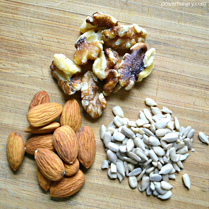sunflower seeds, walnuts and almond on a cutting board