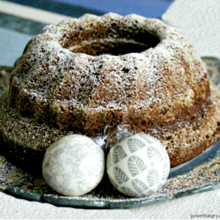 chickpea flour gingerbread bundt cake on a serving plate with some Christmas ornaments on the plate for decoration.