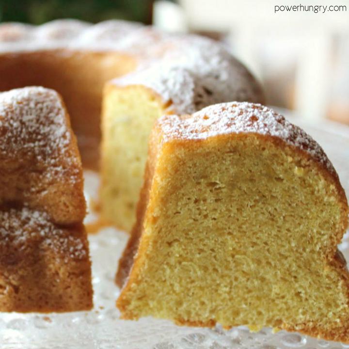 Vanilla Bundt cake on a platter, sliced, and sprinkled with confectioners' sugar