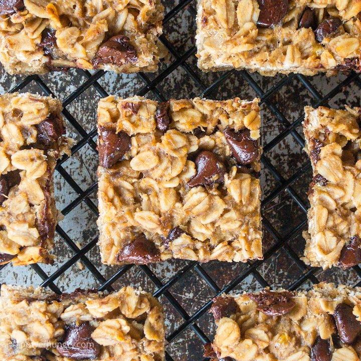 Chocolate chip peanut butter banana oat bars on a black metal cooling rack, shot from overhead