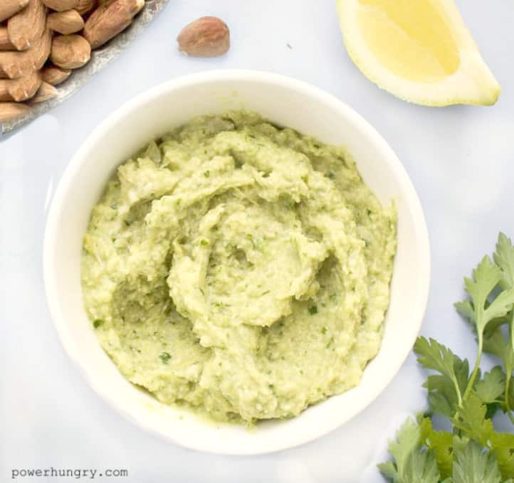 healthy artichoke heart hummus in a white bowl with parsley, lemon and almonds alongside
