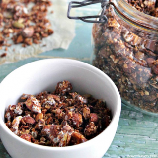 oil-free chocolate granola in a white bowl with more granola in background