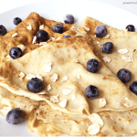 flourless blender oat crepes on a white plate with blueberries
