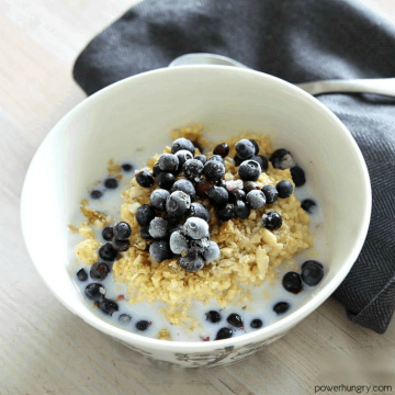 overnight brown rice porridge, made in a slow cooker, in a white bowl topped with milk, walnuts and blueberries