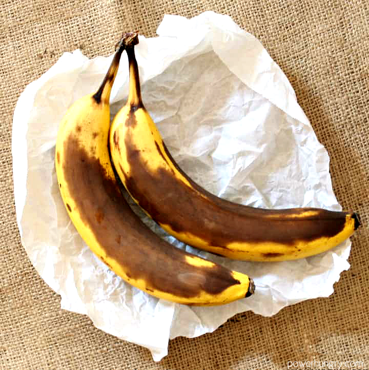 2 very ripe bananas on a piece of white parchment paper, atop a piece of burlap