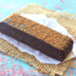 a single chocolate black bean protein bar on a piece of parchment paper