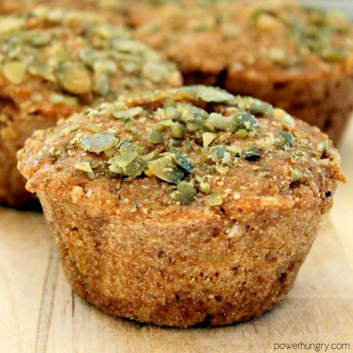 close-up of a banana oat muffin topped with finely chopped pepitas.