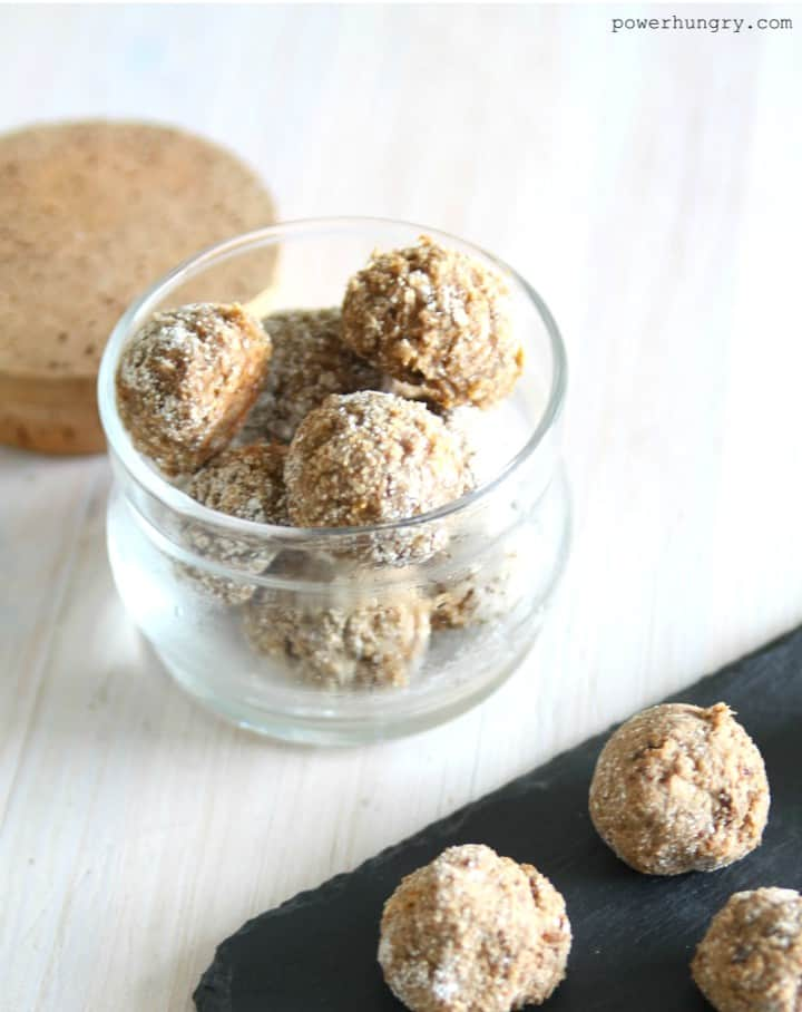 Almond Butter Coconut Flour balls in a glass jar, with more balls on a piece of black slate