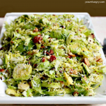 lemony shredded brussels sprouts salad on a white dish atop a white linen napkin