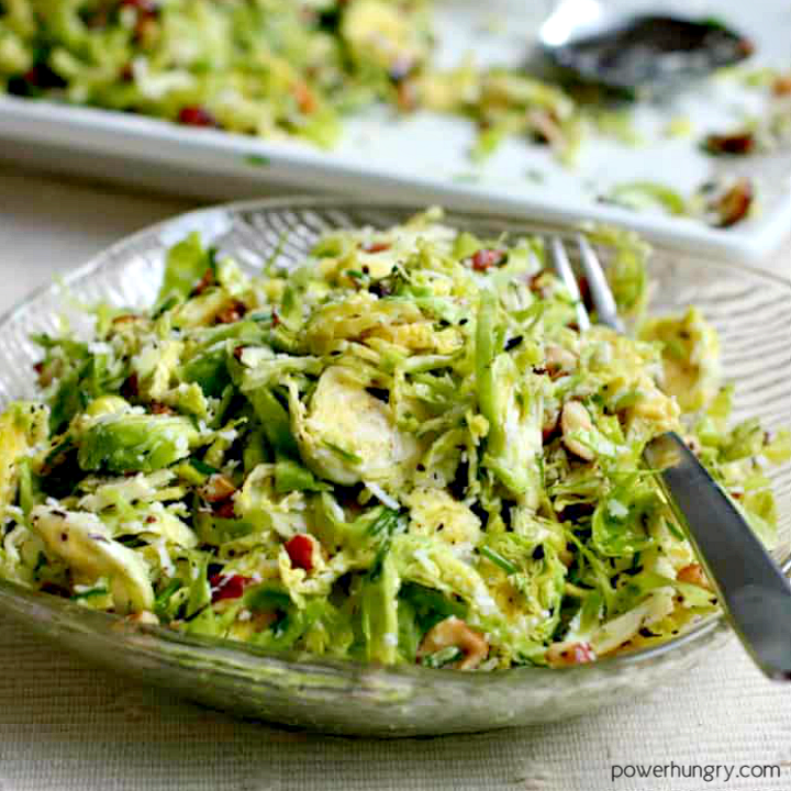shredded brussels sprouts salad in a salad plate with a serving platter in the background