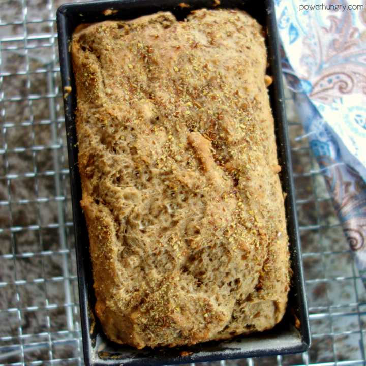 baked quinoa and almond soda bread in a metal baking tin, cooling on a wire cooling rack.