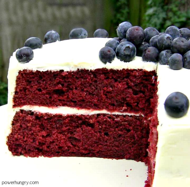 layered vegan gf red velvet cake on a white pedestal