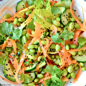 asian edamame carrot salad in a white bowl, sprinkled with black sesame seeds