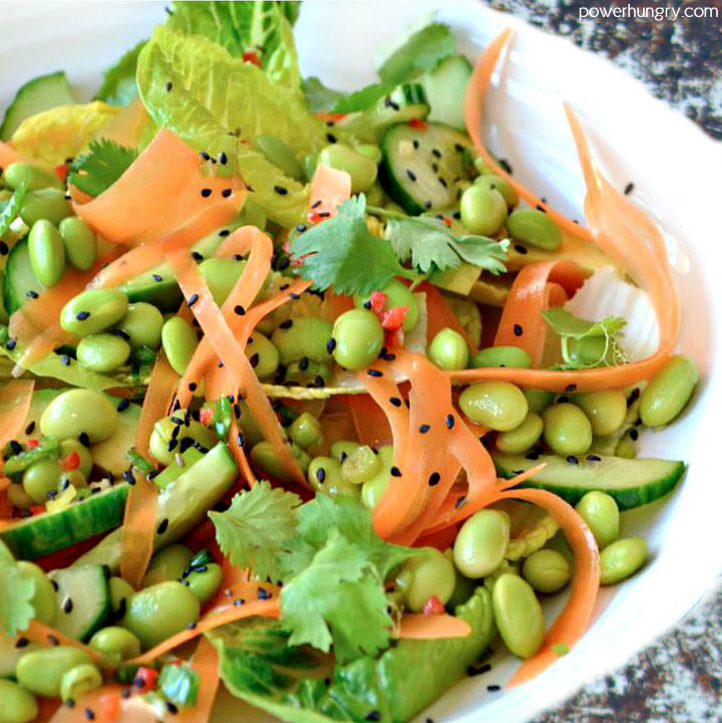 edamame carrot salad in a white bowl with sesame seeds sprinkled on top