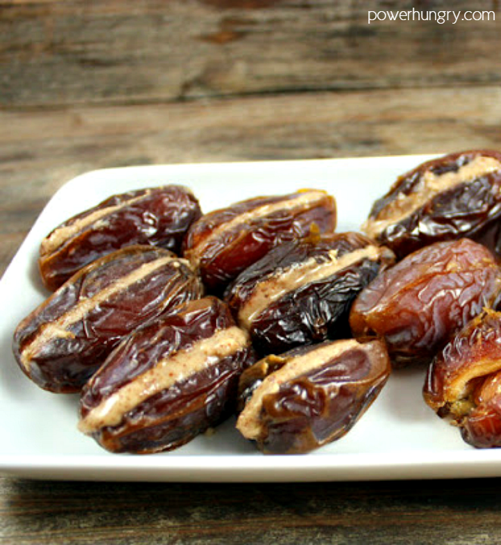 medjool dates stuffed with almond butter , sitting on a white plate
