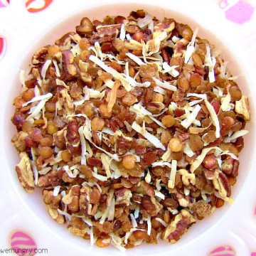 red lentil granola in a white bowl atop a pink and orange napkin