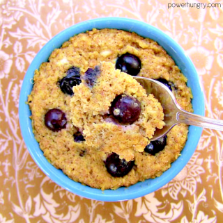 overhead shot of a vegan blueberry oat mug muffin with a spoon