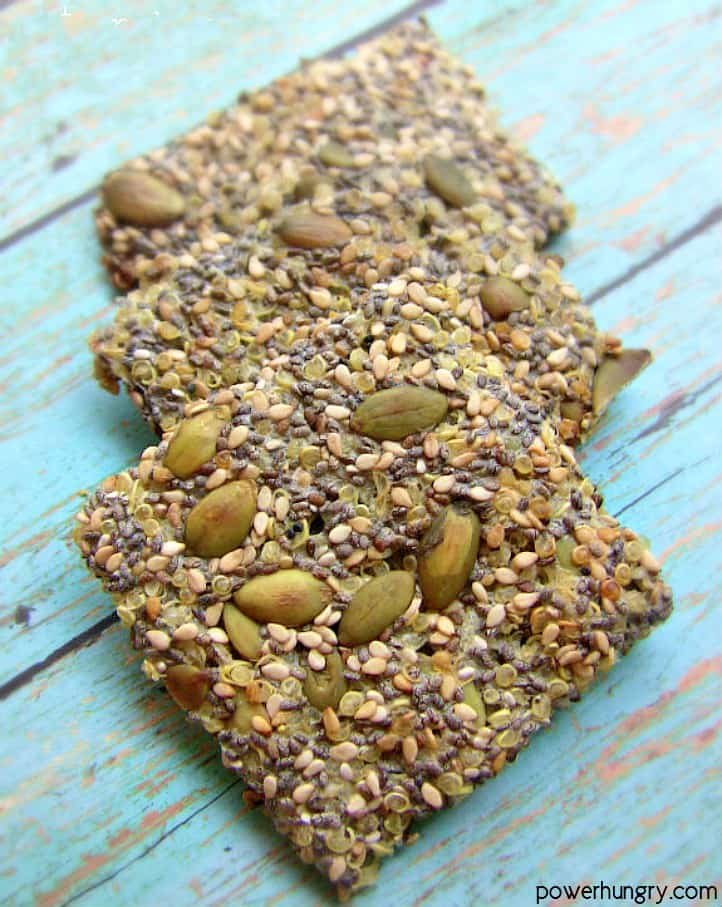 3 multi-seed quinoa crackers on a piece of blue painted wood
