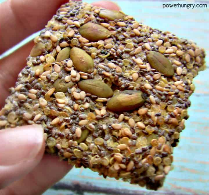 close-up of a hand holding a quinoa cracker with various seeds