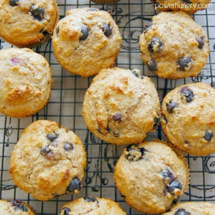 Paleo almond flour muffins, with blueberries added, on a black cooling rack