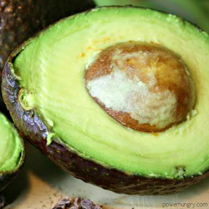 close up of and avocado, halved, on a cutting board