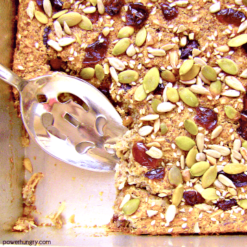 coconut flour baked porridge in a square metal baking pan, topped with cranberries and various seeds