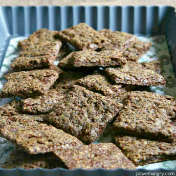 a small heap of teff crackers piled into a decorative baking dish