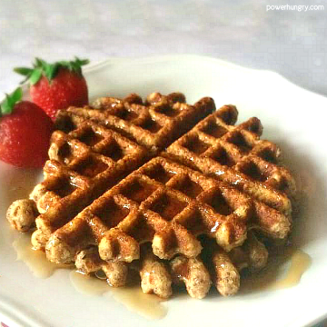 almond flour waffles on a white plate with strawberries and syrup