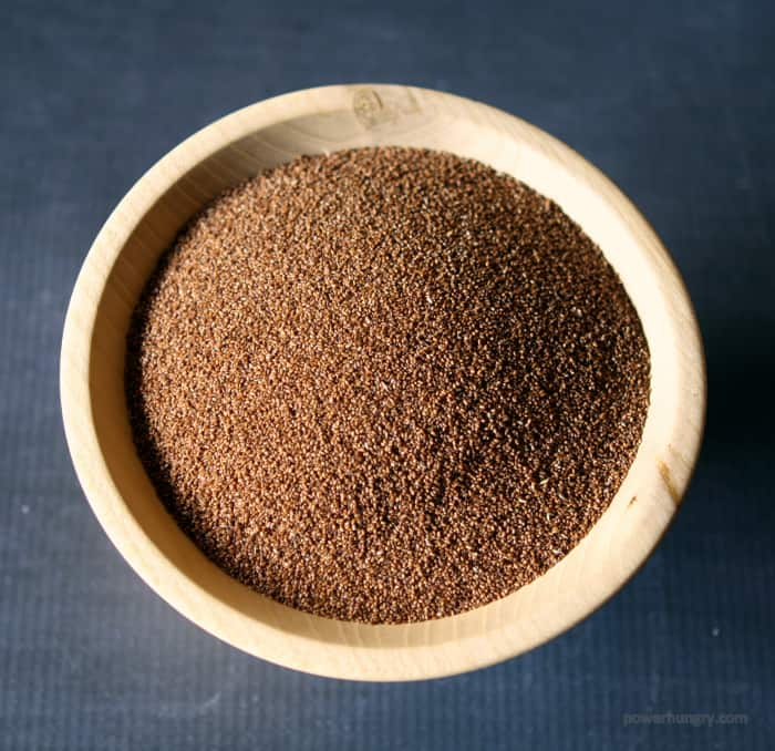 whole grain, uncooked teff grains in a wooden bowl