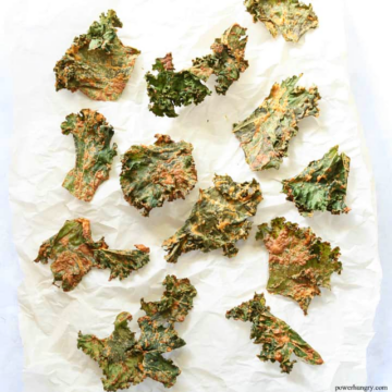 coated kale chips on white parchment paper