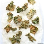 overhed shot of kale chips on white parchment paper