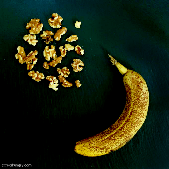 an overripe banana and toasted walnuts on a piece of slate