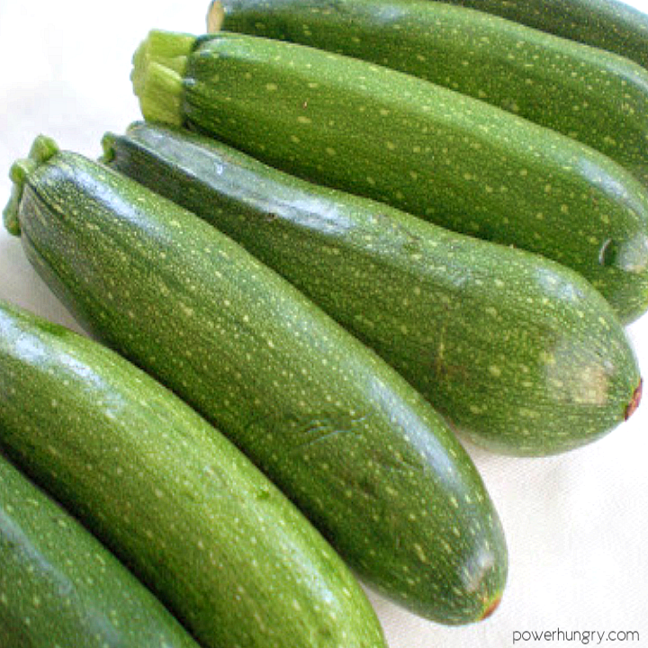several large summer garden zucchini on a white background
