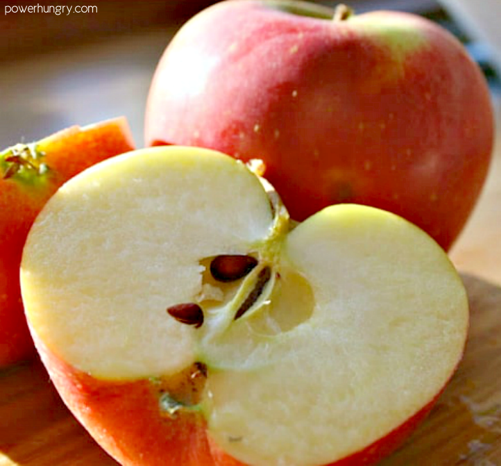 tart sweet Gala apple , sliced in half on a cutting board