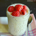 a jar full of banana chia overnight oats, filled to the brim and topped with fresh raspberries