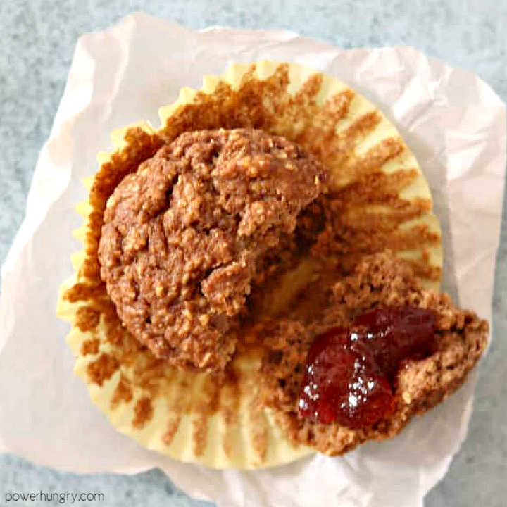 vegan oat bran muffin on a piece of parchment paper, one piece spread with jam