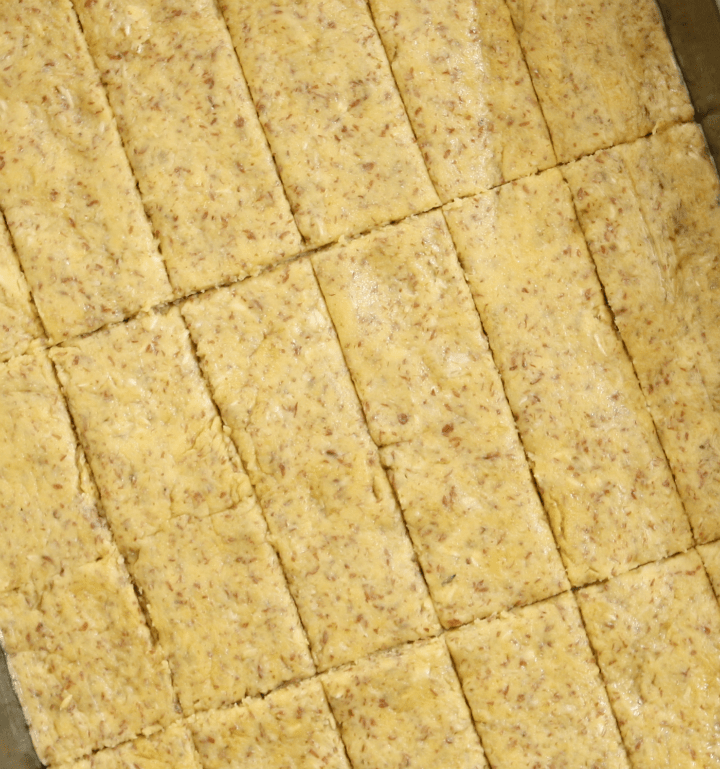unbaked almond oat & chickpea flour crackers cut into pieces and ready to be baked on a baking sheet