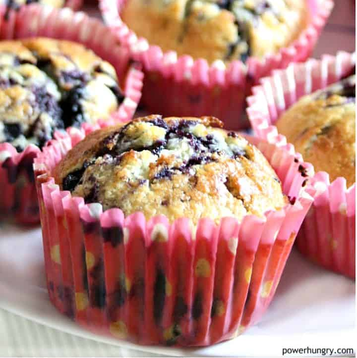 white plate with vegan oat blueberry muffins in pink muffin liners