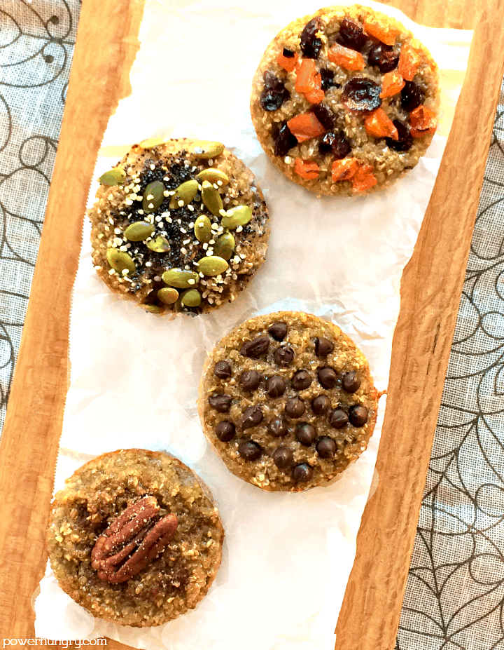 overhead shot of 3-ingredient banana quinoa muffins on a piece of parchment paper, atop a cutting board, with assorted toppings