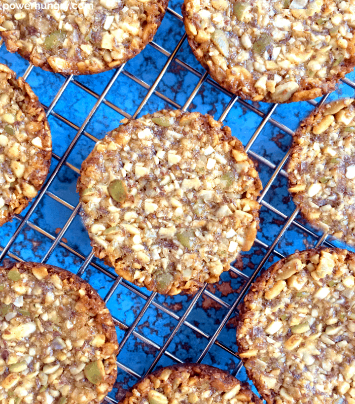 overhead shot of crunchy nuts and seeds breakfast cookies on a wire cooling rack atop a blue background