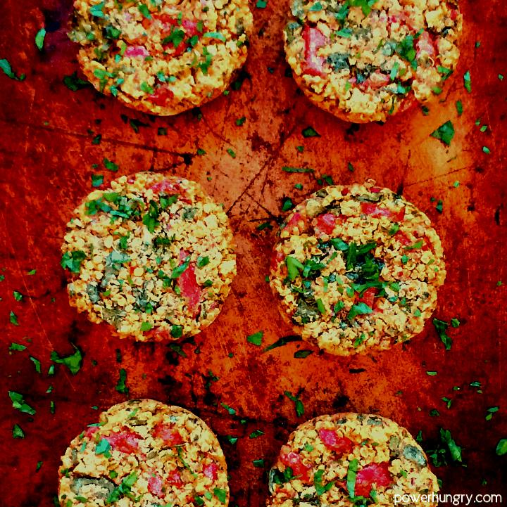 overhead shot of vegan quinoa muffin tin burgers on an aged baking sheet