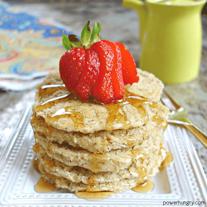 stack of vegan oat pancakes on a square white plate with a slied strawberry on top