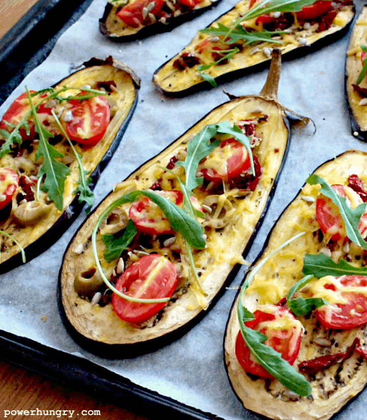 close-up of eggplant pizza slices topped with arugula and cherry tomatoes
