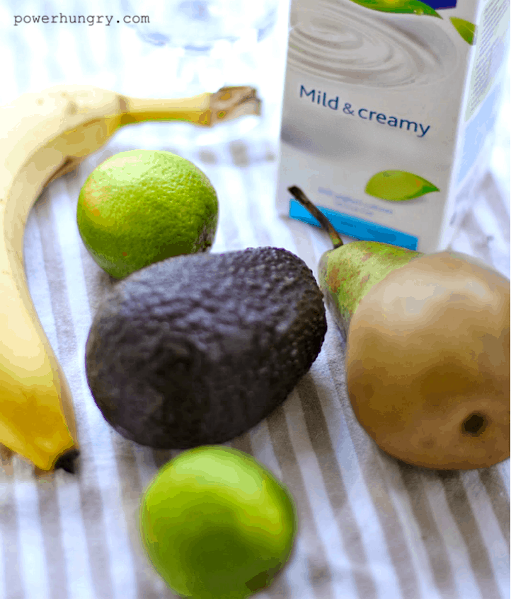 ingredients for avocado banana and per smoothies on a striped napkin