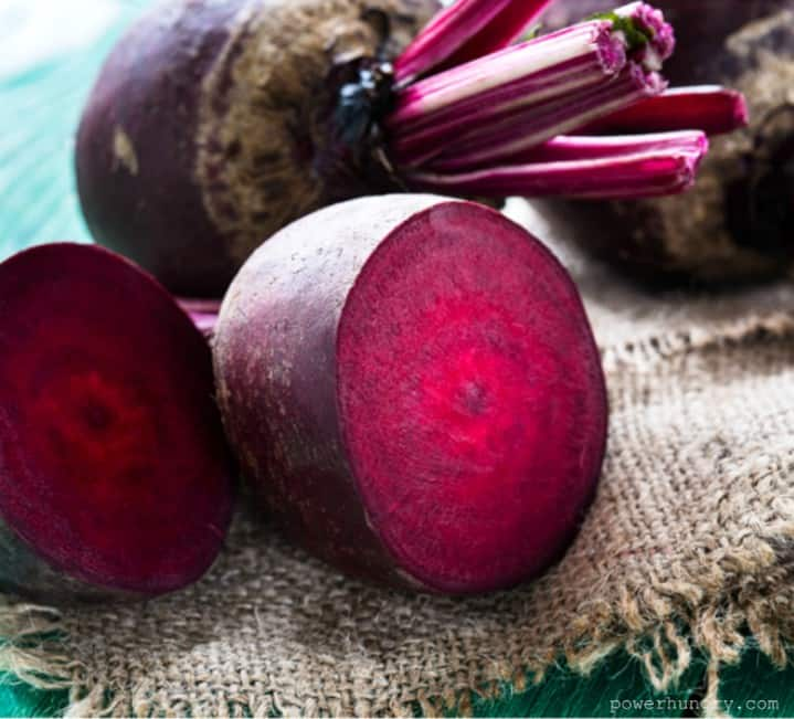 fresh raw beets, with one slice in half, atop a piece of burlap