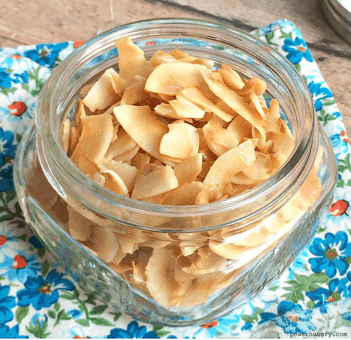 baked coconut chips in a glass jar on a floral napkin