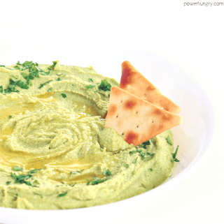 healthy broccoli hummus in a white serving bowl with some healthy chips