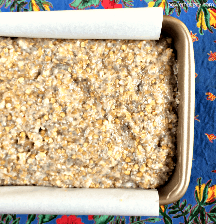 overhead shot of buckwheat flax chia bread batter in a small loaf pan, a blue napkin in the background